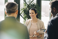Smiling female entrepreneur discussing with male colleagues while standing in office - MASF08092