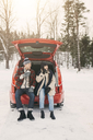 Full length of friends having coffee while sitting in car trunk on snowy field - MASF08107