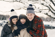 Cheerful friends in warm clothing embracing at park during winter - MASF08119