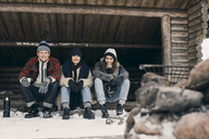 Full length portrait of friends sitting in log cabin against trees during winter - MASF08134