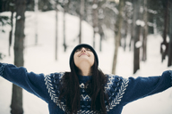 Happy woman standing with arms raised on snowy field during winter - MASF08143