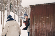 Man throwing snowball while standing with friend by log cabin during winter - MASF08146