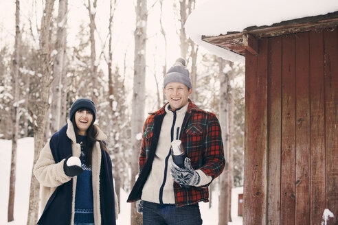 Portrait of happy friends holding snowball while standing by log cabin during winter - MASF08149