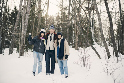 Full length of smiling friends standing against trees on snow covered field - MASF08155