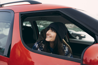 Smiling woman looking away while sitting in red car - MASF08164