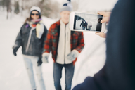 Woman photographing friends through smart phone on field during winter - MASF08182