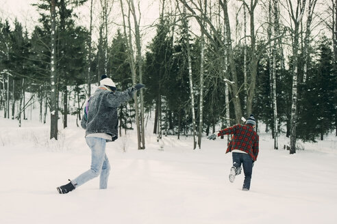 Playful friends running by trees on snow covered landscape - MASF08188