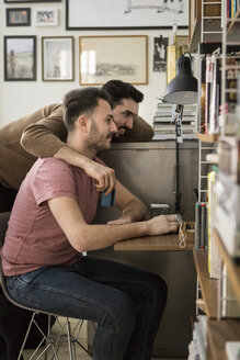 Side view of gay couple shopping online through computer at home - MASF08191