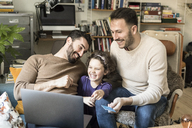 Happy fathers with daughter shopping online on laptop through credit card while sitting on chairs at home - MASF08194