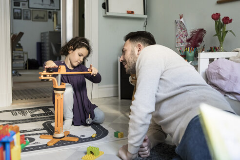 Father looking at daughter playing with crane toy in living room at home - MASF08197
