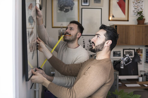 Young man with tape measure assisting partner while hanging painting on wall - MASF08200