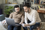 Gay couple shopping online with credit card through laptop while relaxing on chairs at home - MASF08209