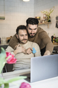 Homosexual couple doing online shopping through laptop in kitchen at home - MASF08212