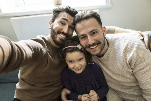 Smiling fathers and daughter taking selfie while sitting on sofa in living room at home - MASF08215