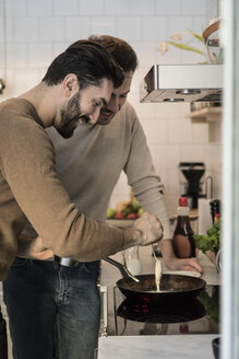 Smiling gay man standing with partner while pouring batter in cooking pan at kitchen - MASF08230