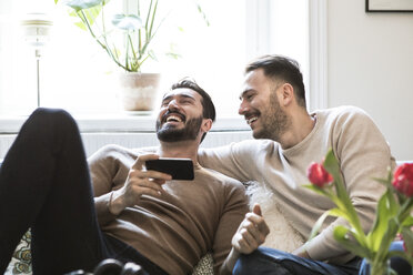 Cheerful gay couple with smart phone sitting on sofa against window at home - MASF08233