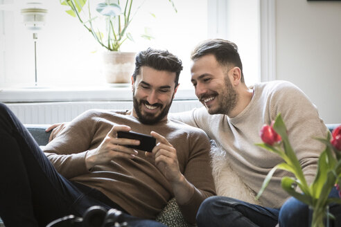 Smiling young men looking at smart phone while sitting on sofa at home - MASF08236