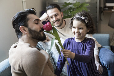 Smiling daughter making father smell tulip while sitting with man on sofa in living room - MASF08239