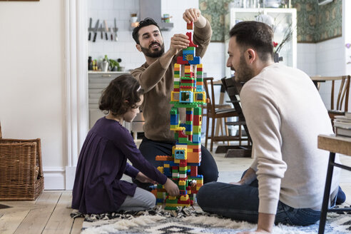 Happy gay men playing blocks with daughter at home - MASF08242