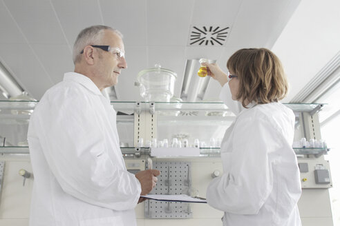 Scientists working in laboratory, looking at yellow liquid in vial - CUF40065