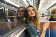 Portrait of smiling young woman and her mirror image in underground train - AFVF00742