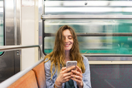 Portrait of smiling young woman in underground train looking at smartphone - AFVF00745
