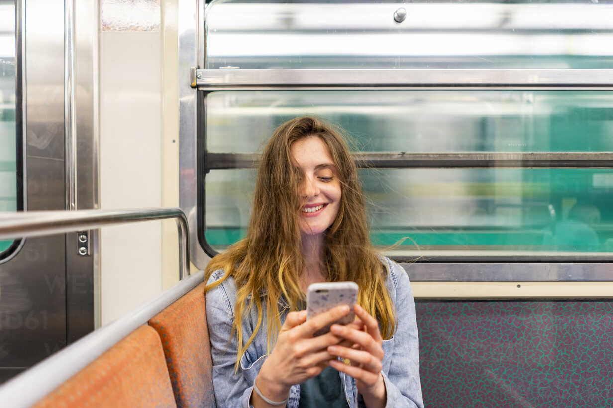 Portrait of smiling young woman in underground train looking at smartphone - AFVF00745 - VITTA GALLERY/Westend61