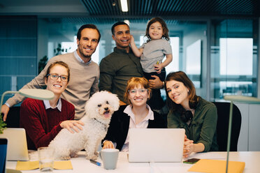 Portrait of smiling business team with kid and dog at creative office - MASF08255