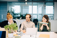 Cheerful business colleagues discussing while sitting at desk in creative office - MASF08258