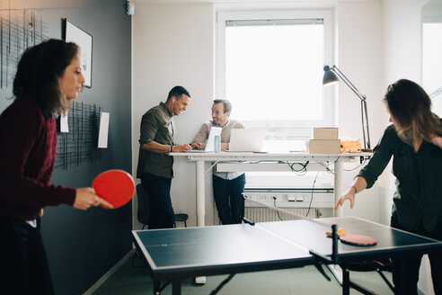 Female professionals playing table tennis while male colleagues using laptop at creative office - MASF08285