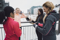 Happy women talking while standing on bridge during winter - MASF08315