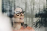 Close-up of thoughtful businesswoman wearing eyeglasses seen through window - MASF08345