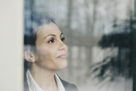 Close-up of thoughtful businesswoman seen through glass window at office - MASF08348