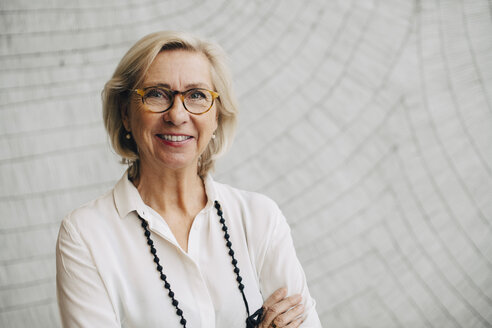 Portrait of smiling senior businesswoman standing against wall in office - MASF08378