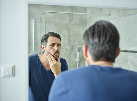 Serious man looking in bathroom mirror - CVF00946