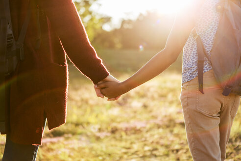 Midsection of mother and daughter holding hands at park during sunset - MASF08438