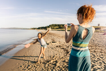 Rear view of woman photographing playful daughter standing on shore at beach against sky - MASF08444