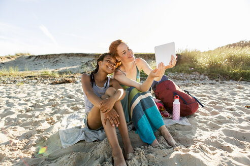Full length of happy mother taking selfie with daughter while sitting at beach against sky - MASF08450