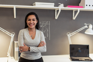 Portrait of confident businesswoman with arms crossed standing against wall at creative office - MASF08453