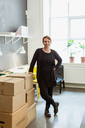 Portrait of smiling businesswoman standing by cardboard boxes stack against window at creative office - MASF08474