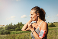Woman listening music through mobile phone on arm band while exercising against sky - MASF08540