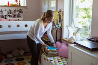 Woman stacking books on table while cleaning bedroom at home - MASF08546