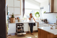Smiling woman talking on mobile phone while standing in kitchen - MASF08552