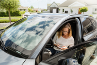 High angle view of woman using mobile phone while sitting in car on sunny day - MASF08558