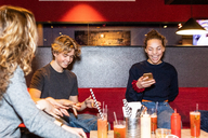 Cheerful multi-ethnic teenage friends enjoying while sitting on sofa at restaurant - MASF08567
