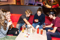 Happy multi-ethnic teenage friends sitting on sofa with drinks while using smart phone at restaurant - MASF08570