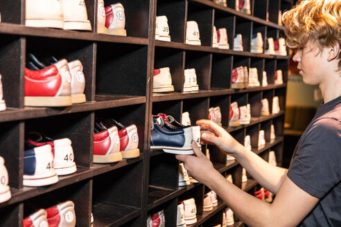 Side view of blond teenage boy holding bowling shoes at wooden rack - MASF08576