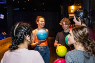 Cheerful multi-ethnic teenagers talking while holding bowling balls - MASF08588