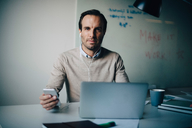 Portrait of confident businessman sitting with smart phone and laptop at desk in creative office - MASF08600