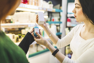 Two women in a cosmetics shop trying products - WPEF00659